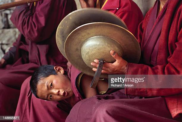 young monk peering out from group at tengboche monastery during annual mani rimdu festival. - mani rimdu festival stock pictures, royalty-free photos & images