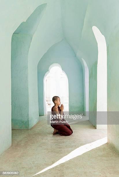 Young monk (13-15) praying inside temple corridor, Burma
