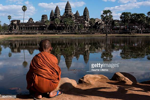 A young monk sits in front of the Angkor Wat temple reflected on a lake on January 1 2016 in Siem Riep Cambodia Angkor was the capital city of Khmer...