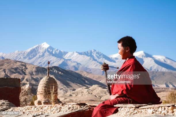 Young monk spinning prayer wheel, Upper Mustang, Nepal