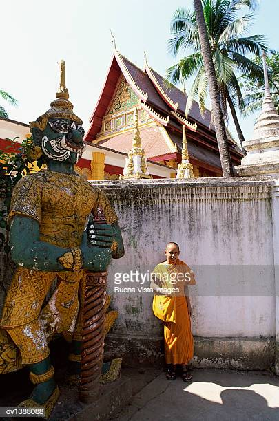 Young Monk Standing Next to a Temple Statue, Vientaine, Laos
