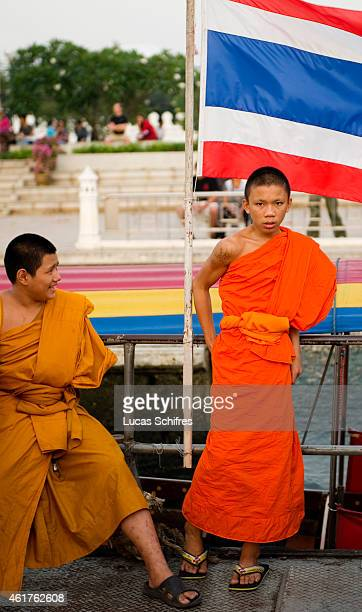 A young monk stands by a by a Thai national flag on a boat on December 18 2010 in Bangkok Thailand
