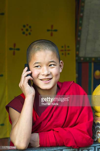 Young monk with a mobile phone, Bhutan.