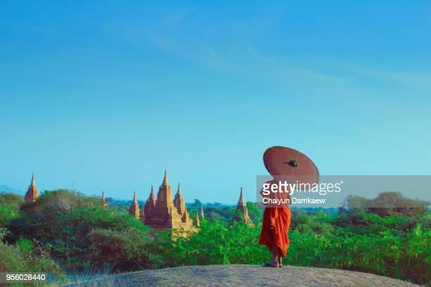 ํYoung Monk with Umbrella Overlooks Bagan Temples, Myanmar.
