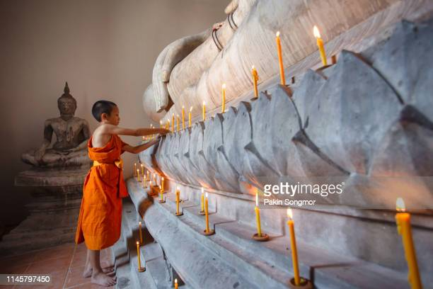 young monk worship the buddha with candle and light at wat phutthai sawan - wat stock pictures, royalty-free photos & images