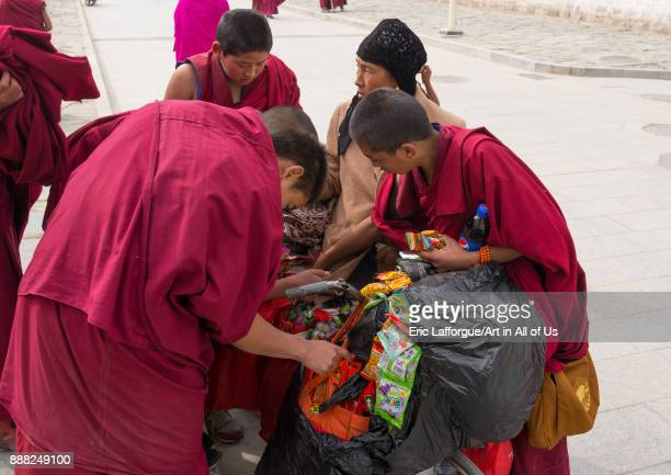 Young monks buying candies and food to a hui woman seller Gansu province Labrang China on October 31 2017 in Labrang China