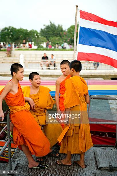 Young monks chat by a Thai national flag on a boat on December 18 2010 in Bangkok Thailand