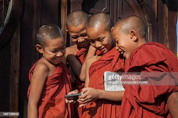 CONTENT] Young monks gathering around smartphone at bagan Myanmar