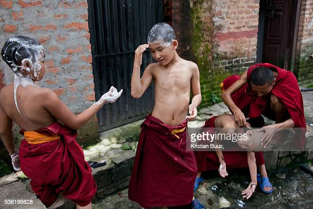 Young monks in a Tibetan monestary at the Swayambhunath temple complex also called the Monkey Temple The young boys are having their hair shaved by...