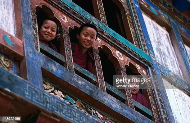 young monks peer from the window of trongsa dzong. - trongsa district stockfoto's en -beelden