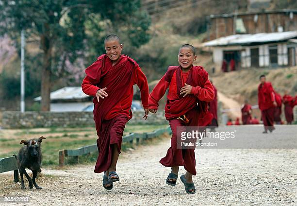Young monks run back to class at the Dechen Phodrang monastery April 2 2008 in Thimphu Bhutan About 475 monks reside at the government runmonastery...