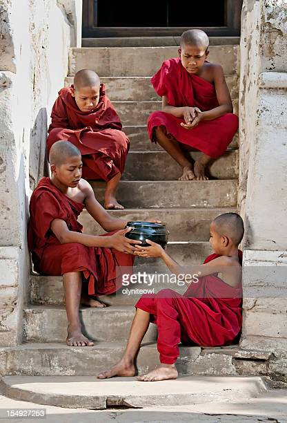 young monks sitting on a stairway - yangon stock pictures, royalty-free photos & images
