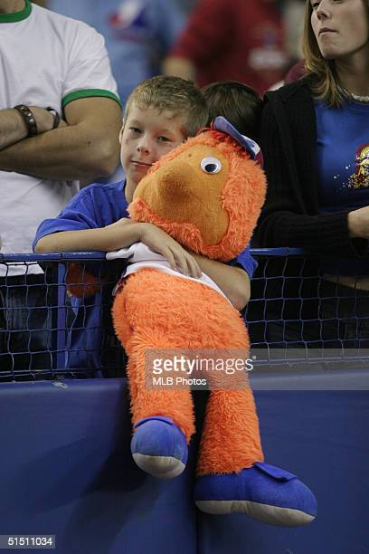 A young Montreal Expos fans hugs his 'Youppi' plush doll during the final Montreal Expos home game ever at Olympic Stadium against the Florida...
