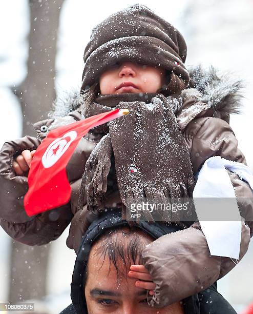 Young Montrealer holding a Tunisian flag during a rally on a cold afternoon in Montreal Quebec Canada January 15 2011 More than a thousand people...