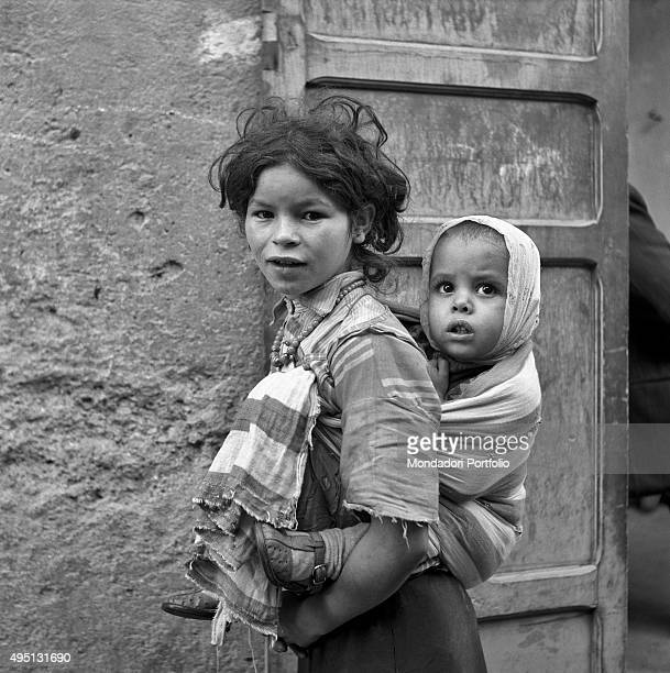 A young Moroccan girl curiously looks at the camera while she is carrying a child on her back in these years some Moroccan women have started to...