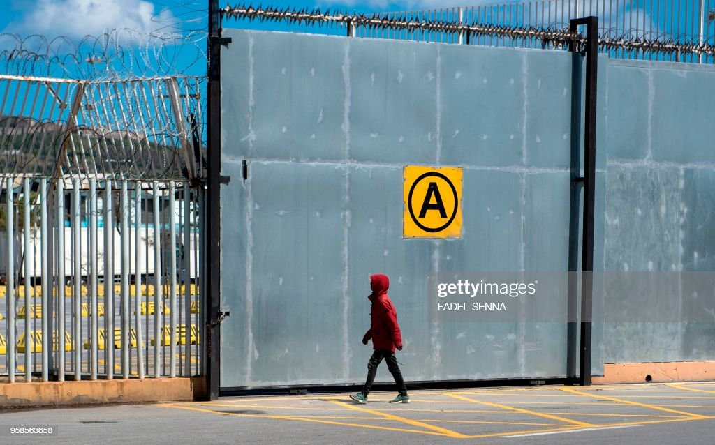 A young Moroccan walks toward a fence at the harbour of the port city of Ceuta,a Spanish enclave perched on the northernmost tip of Morocco, on April 11, 2018, as he tries to reach a boat sailing toward Europe. - In order to reach Ceuta or Melilla, another Spanish enclave, migrants must first scale the barbed wire fences which mark the only land borders between Europe and Africa. Those under 18 are hoping to benefit from European legislation which gives them greater protection than adult migrants and limits the chances of their being deported.