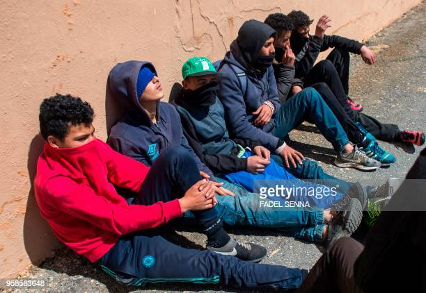 Young Moroccans gather at the harbour of the port city of Ceuta a Spanish enclave perched on the northernmost tip of Morocco on April 11 as they wait...