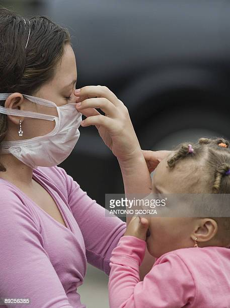 STORY A young mother adjusts her mask while playing with her daughter as they wait to receive medical attention in Rio de Janeiro on July 23 2009...