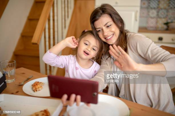 a young mother and a sweet daughter greet their family - mother daughter webcam stock-fotos und bilder