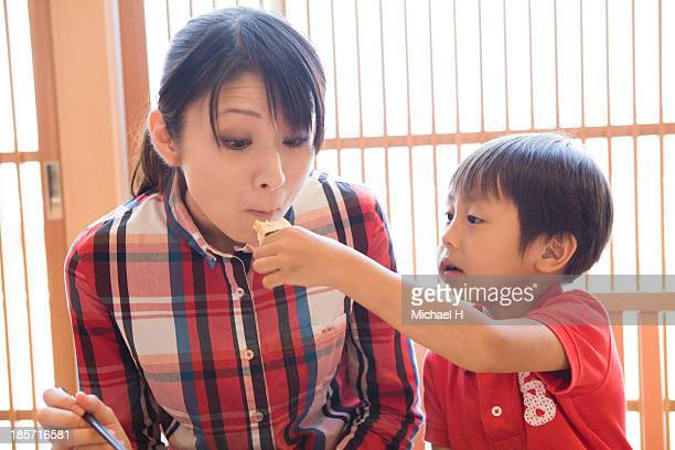 young mother and child eating SUSHI