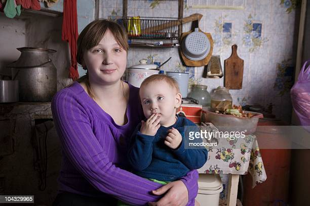 young mother and child sit in kitchen interior - armoede stockfoto's en -beelden