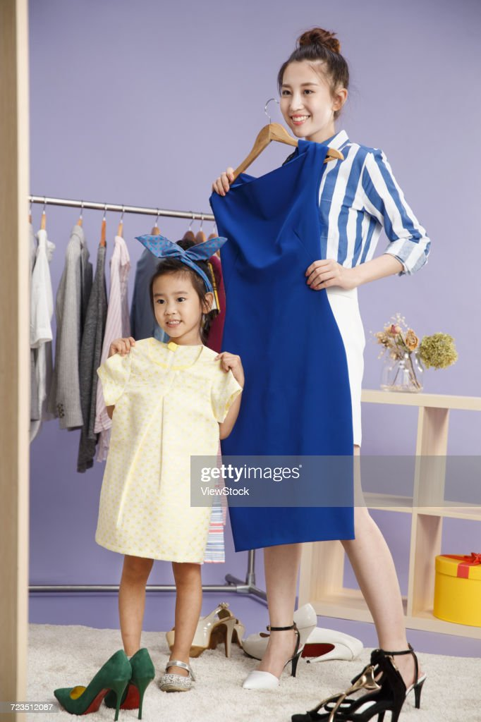 Young mother and child try on clothes : ストックフォト