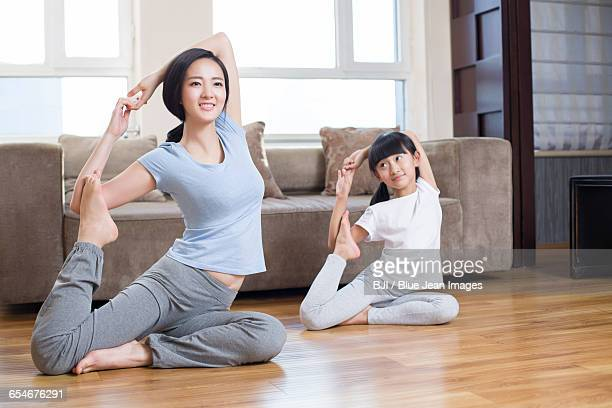 Young mother and daughter doing yoga at home
