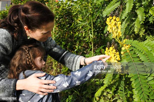 Young mother and daughter examine plants and flowers