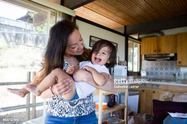 Young mother and daughter playing inside and laughing