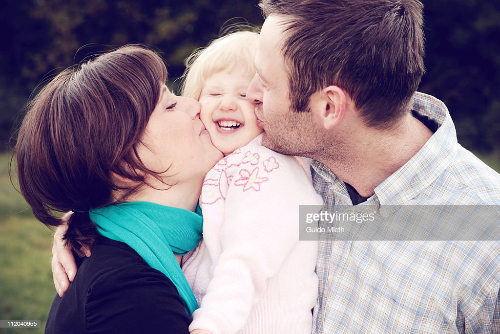 Young mother and father kissing her little girl : Stock Photo