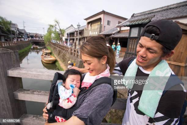 笑顔で女の赤ちゃんを見て父と若い母 - 国際連合教育科学文化機関 ストックフォトと画像