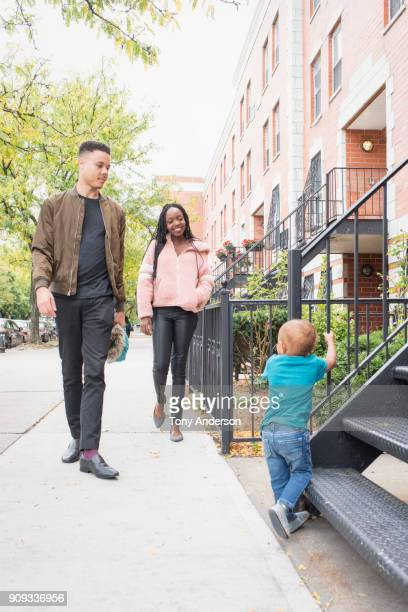 Young mother and father walking with infant daughter in city neighborhood