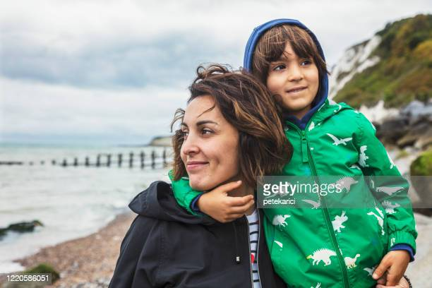 a young mother and her cute little son are walking by a sea - mother stock pictures, royalty-free photos & images