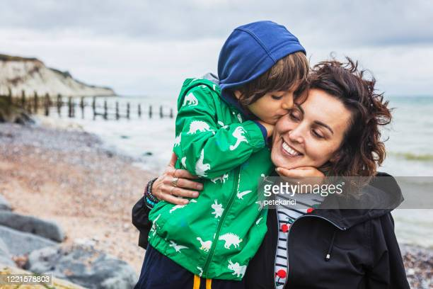 a young mother and her cute little son are walking by a sea - single mother stock pictures, royalty-free photos & images
