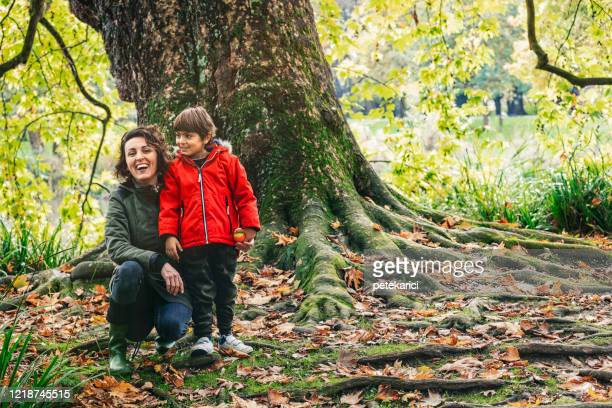 young mother and her cute little son walking in a park - strathclyde stock pictures, royalty-free photos & images