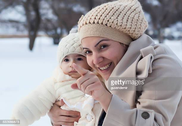 Young mother and her daughter in a winter day