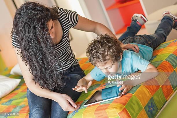 giovane madre e il suo ragazzino utilizzando tavoletta digitale - pjphoto69 foto e immagini stock