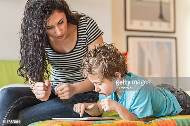 young mother and her little boy using digital tablet - pjphoto69 stock pictures, royalty-free photos & images