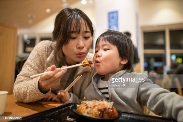 young mother and her little son blowing to takoyaki before eating, - takoyaki stock pictures, royalty-free photos & images