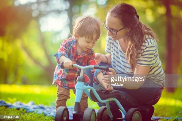 la giovane madre e suo figlio in runbike nel parco estivo - incoraggiamento foto e immagini stock