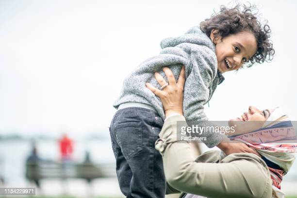 a young mother and her son playing - emigration and immigration stock pictures, royalty-free photos & images