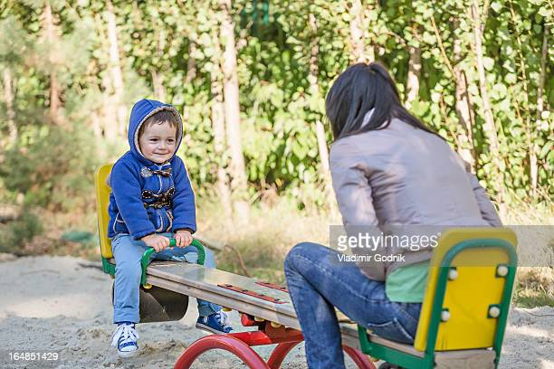 A young mother and her young son on a seesaw at a playground