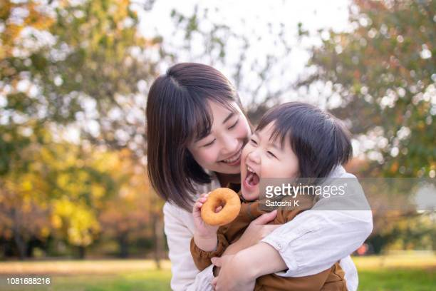 young mother and son eating doughnut in public park with full of fun - asian stock pictures, royalty-free photos & images