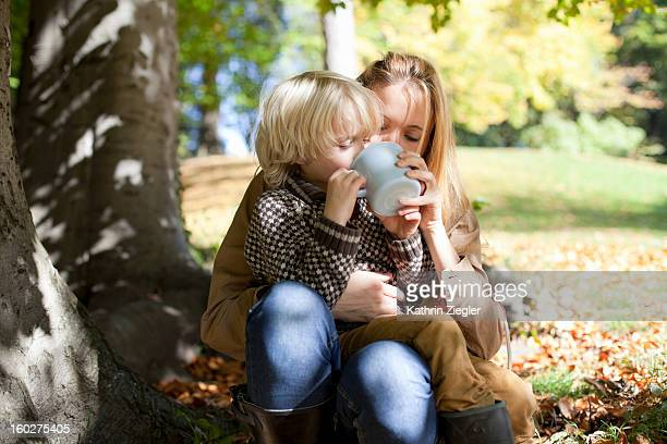 young mother and son in the park, drinking tea