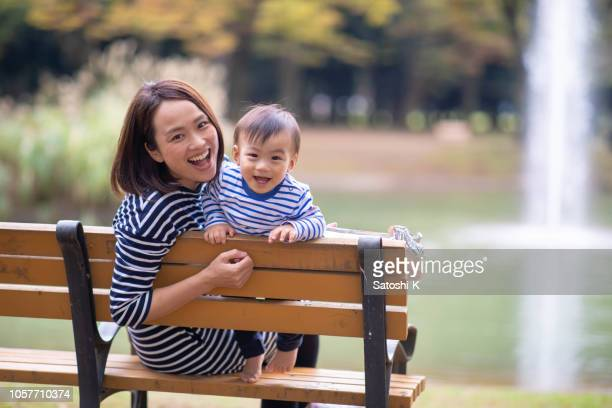 young mother and son looking at camera in public park - japanese mom stock photos and pictures