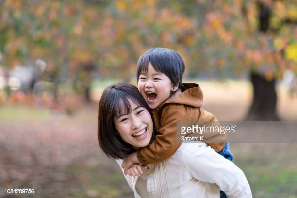 young mother and son playing together in public park - east asian ethnicity stock pictures, royalty-free photos & images