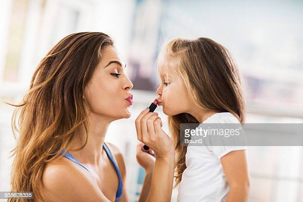 young mother applying lipstick on her daughter. - lipstick stock pictures, royalty-free photos & images