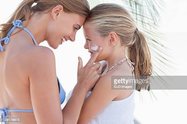 Young mother applying suntan lotion on daughter's cheek