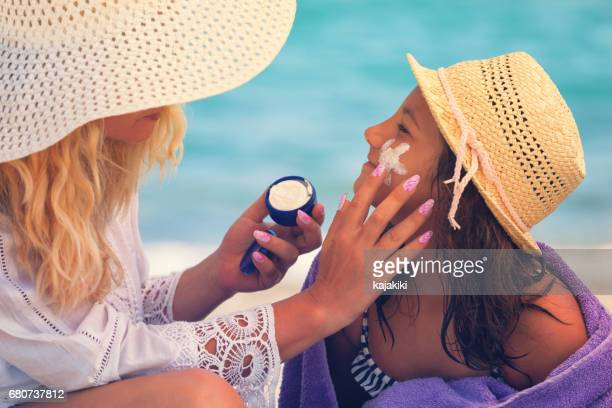 Young Mother Applying Suntan Lotion On Daughter's Face