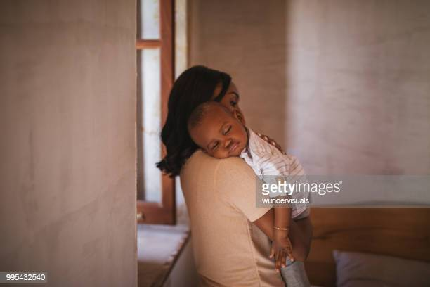 young mother at home rocking baby to sleep with lullaby - cute black newborn babies stock photos and pictures